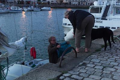 Françoise rend le voile plié à Pieric qui le met dans son sac sous le regard du chien.