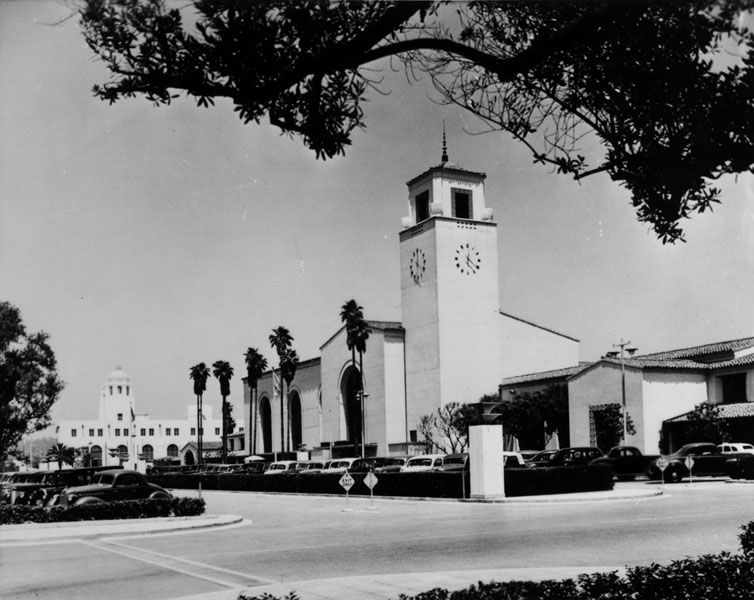 . Exterior view of Union Station located at 800 North Alameda Street, in Los Angeles. View also shows the parking facilities in front of the station.   (Los Angeles Public Library)