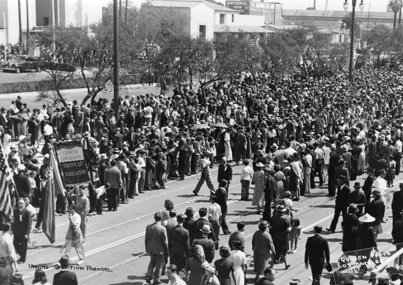 . A crowd lined up to see the Union Station opening day parade on May 3, 1939. A banner for the Chinese Consolidated Benevolent Association is visible.   (Los Angeles Public Library)