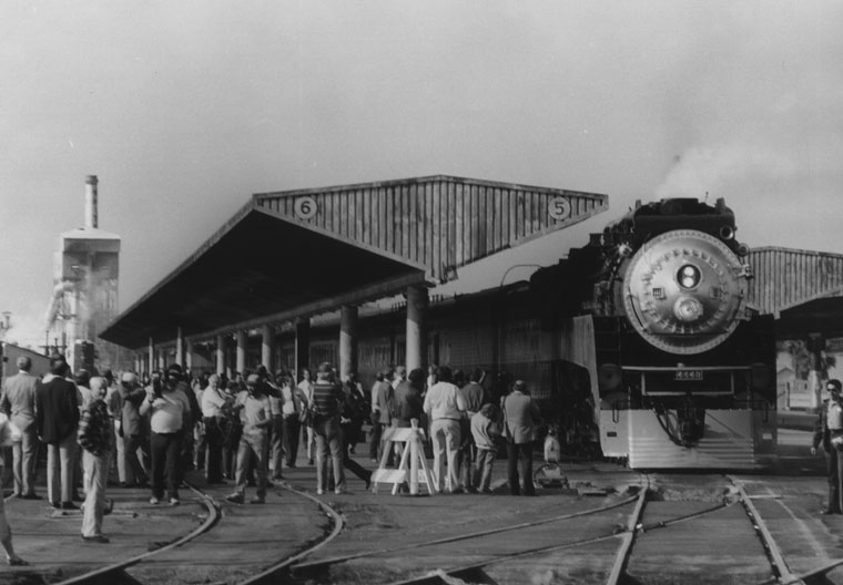 . A train is standing at the boarding platform at Los Angeles\' Union Station. Some people in the crowd watching carry cameras.   (Los Angeles Public Library)