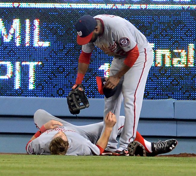 . Nationals centerfielder Denard Span looks over Bryce Harper after he crashed into the right field wall during the 5th inning againt the Dodgers May 13, 2013 in Los Angeles, CA.  Harper left the game after the play and received 11 stitches to close a wound.(Andy Holzman/Staff Photographer)