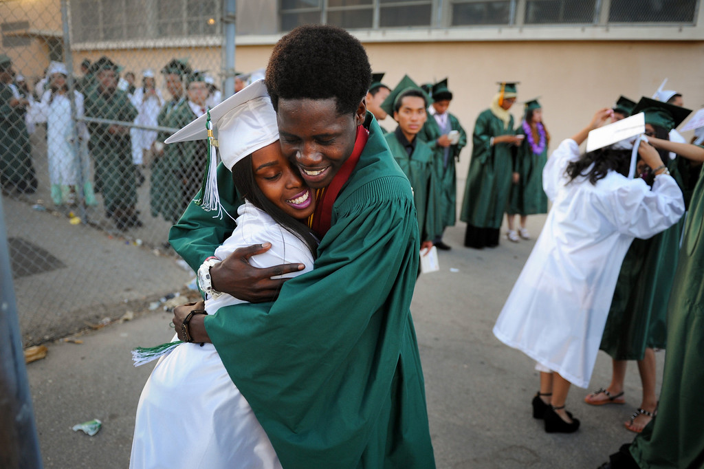 . Jasmine Haynes gets a hug from Nusku Utley-Sanders before the Canoga Park graduation, Friday, June 6, 2014. (Photo by Michael Owen Baker/Los Angeles Daily News)