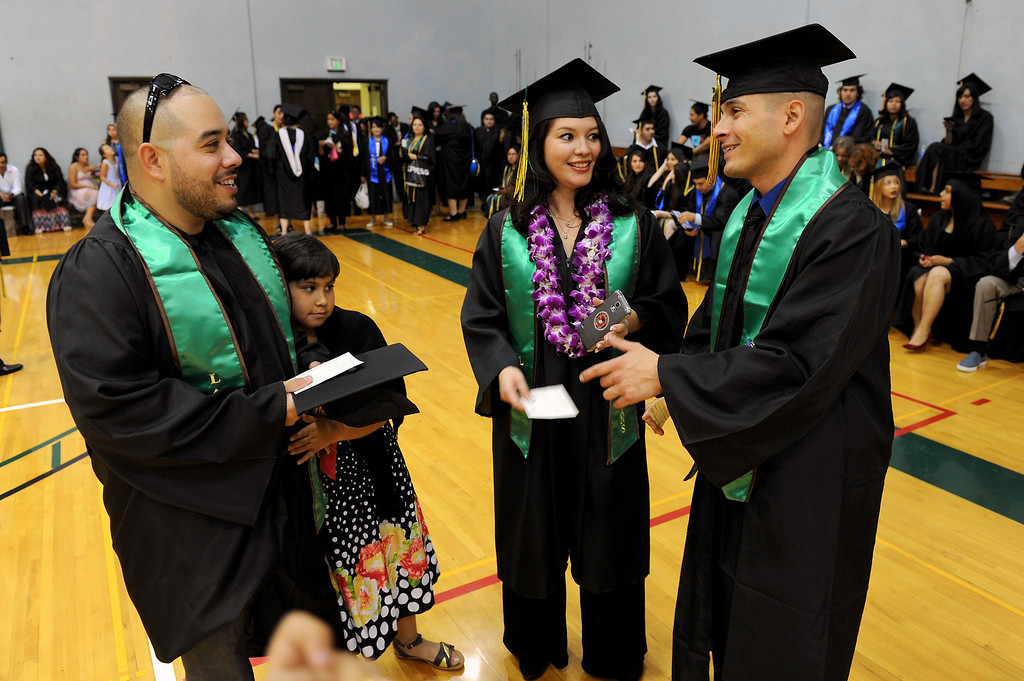 . Marine Corps veteran Jose Padilla, left, stands with his daughter, Kelly Padilla, and talks with fellow Marine Corps veterans Luisa Zamorra and Edwin Gamez before the Valley College graduation, Tuesday, June 10, 2014. (Photo by Michael Owen Baker/Los Angeles Daily News)