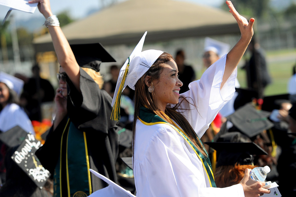 . Lissete Sussoni, right, waves to relatives at the Los Angeles Valley College graduation, Tuesday, June 10, 2014. (Photo by Michael Owen Baker/Los Angeles Daily News)