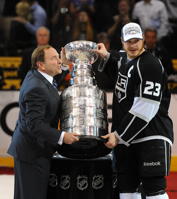 . NHL Commissioner Gary Bettman hands the Stanley Cup to the Kings\' Dustin Brown after beating the Rangers in double-overtime, Friday, June 13, 2014, at Staples Center. (Photo by Michael Owen Baker/Los Angeles Daily News)