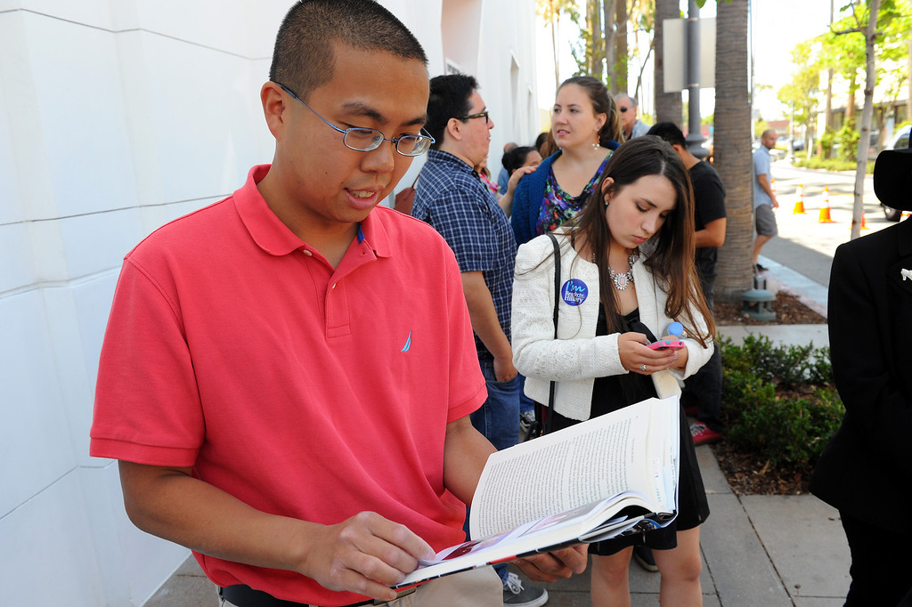 """. Alvin Leung looks through Hillary Rodham Clinton\'s book \""""Hard Choices\"""" while waiting in line four hours for Clinton\'s book signing at Barnes & Noble at The Grove, Thursday, June 19, 2014. (Photo by Michael Owen Baker/Los Angeles Daily News)"""