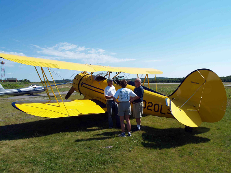 A QUICK BRIEFING<br /> Here's Phil himself giving his first morning's passengers a briefing on the route (they chose the lighthouse tour) and some ins and outs about entering and settling into the rather cramped -- for two -- front cockpit of the Waco. I could tell they were a little nervous about the flight, but excited at the same time, and I envied them. What a beautiful morning for a flight in a biplane!
