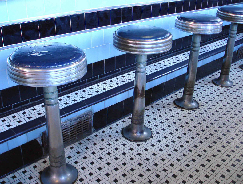 COUNTER STOOLS<br /> You can see what I meant by well-worn in this nice angled shot of the diner's counter stools. Lots of folks have sat on these stools. I wonder who?
