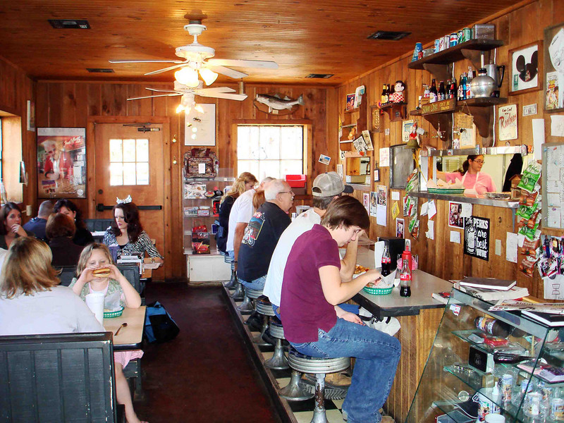 "THE ROCK CAFE INTERIOR<br /> And the place was hopping. As I happened along around 11:30, I managed to just beat the crunch of 25 members of a car club who were scheduled to swarm in. What a break, but as you can see, there were still a ton of folks here. If you look closely on the right, you can see the owner/operator/cook Sally through the stainless steel pass-through window. (A lucky shot. I didn't even plan that.) She runs a tight cafe, she does, telling her kids (the wait staff) to ""Tell those people out there the burgers are just cooked; no medium rare or well done -- none of that crap!"" Yes, ma'am, no problem."