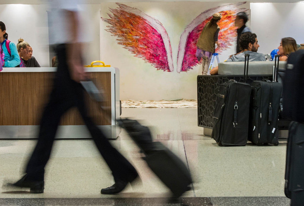 . Local L.A. artist Colette Miller and creator of the Global Angel Wings Project finishes up her angel wings inside the Tom Bradley International Terminal at LAX in Los Angeles CA. Monday, August 22,  2016. Travelers through LAX can snap their own photo with the wings and post to social media using #iflyLAX . (Thomas R. Cordova/Southern California News Group)
