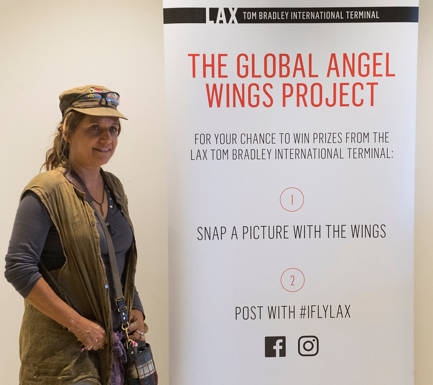 . Local L.A. artist Colette Miller and creator of the Global Angel Wings Project paints wings inside the Tom Bradley International Terminal at LAX in Los Angeles CA. Monday, August 22,  2016. Travelers through LAX can snap their own photo with the wings and post to social media using #iflyLAX . (Thomas R. Cordova/Southern California News Group)