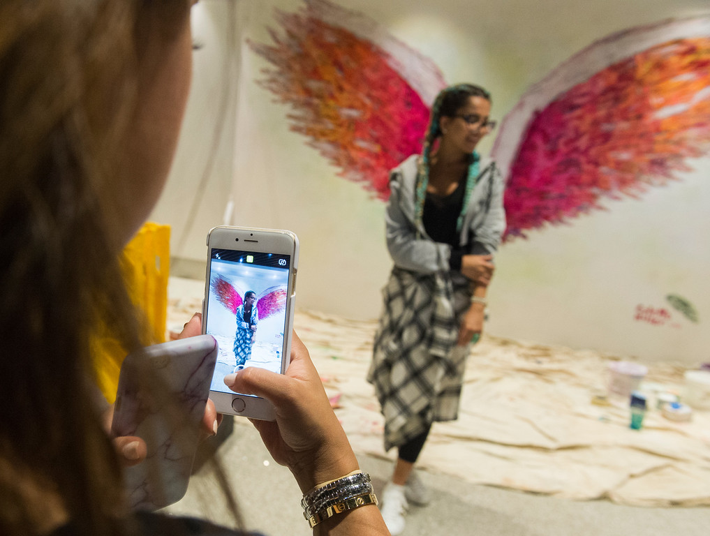 . Sausan Alkadi poses in front of angel wings as local L.A. artist Colette Miller and creator of the Global Angel Wings Project paints wings inside the Tom Bradley International Terminal at LAX in Los Angeles CA. Monday, August 22,  2016. Travelers through LAX can snap their own photo with the wings and post to social media using #iflyLAX . (Thomas R. Cordova/Southern California News Group)