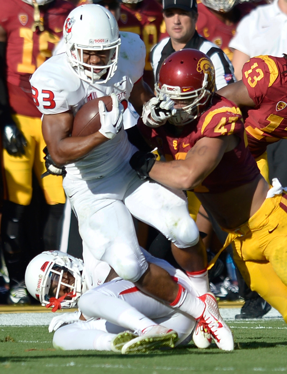. Fresno #33 Marteze Waller is brought down by #47 Scott Felix in the 2nd quarter. USC played Fresno State at the Los Angeles Memorial Coliseum for the first game of the year. Los Angeles, CA. 8/30/2014(Photo by John McCoy Daily News