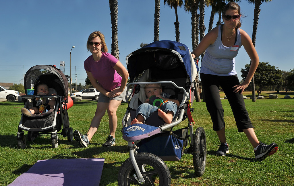 . 9/27/13 - Following a jogging stroller workout, Laura Scott and 13 month old Gavin Scott, left join Jen Urguhart and 16 month old Gavin for stretching.   Long Beach-Stroller Strides gathers moms and their children for fun outdoor exercise at Marine Stadium in Long Beach. For information on classes visit http://longbeach.fit4mom.com/ (Photo by Brittany Murray/Press Telegram)
