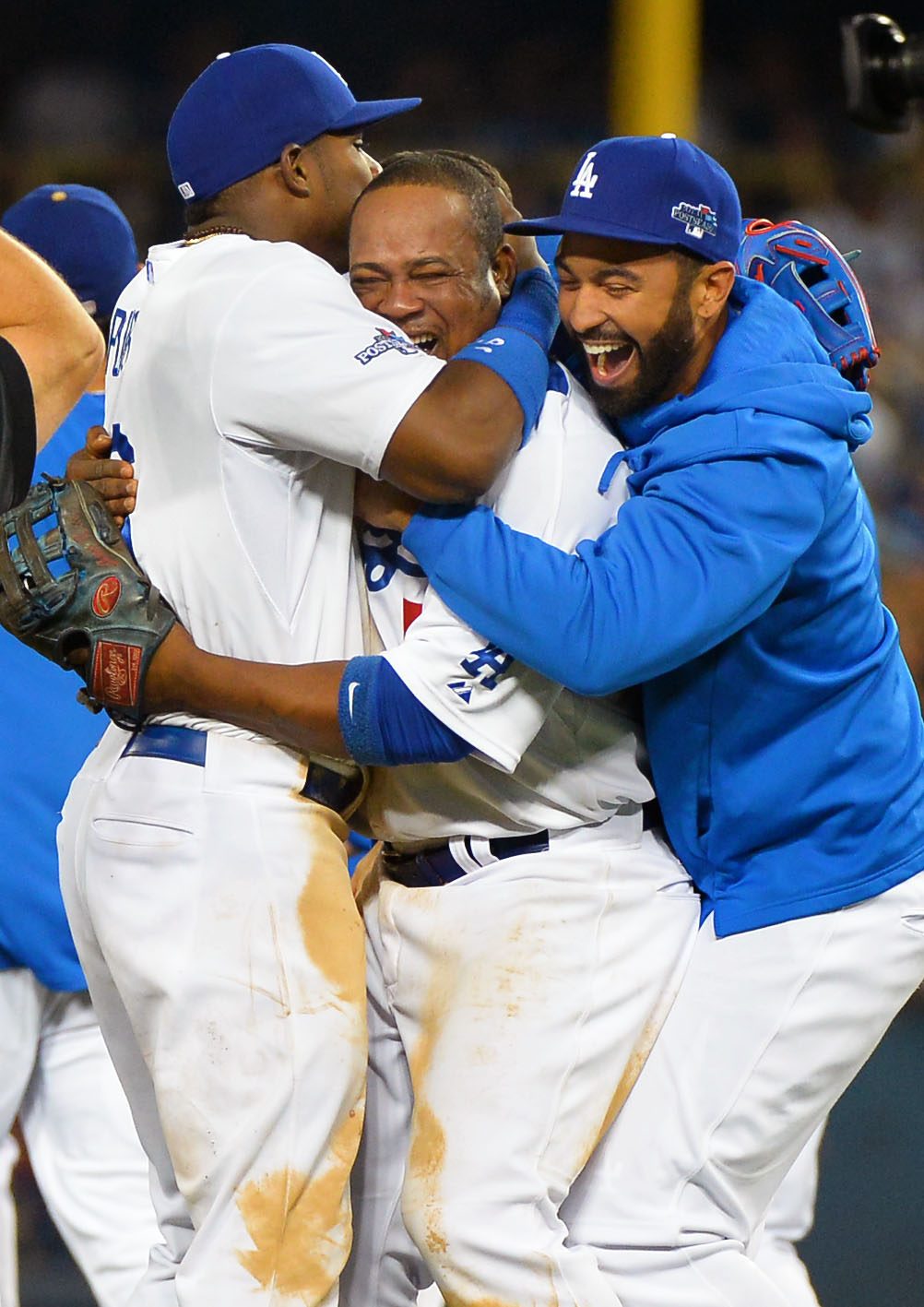 Description of . Matt Kemp and Yasiel Puig celebrate with Juan Uribe follwing their victory over the Braves October 7, 2013.(Andy Holzman/Los Angeles Daily News )