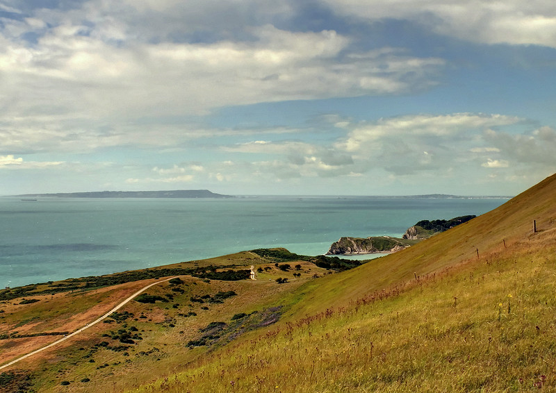 Under the ridge is Lulworth Cove, with the Isle of Portland lying brooding beyond.
