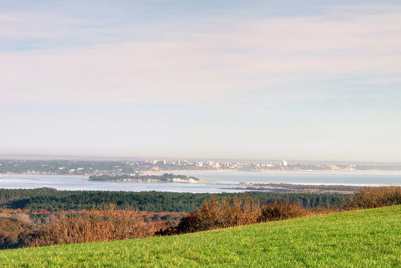 Looking from the ridge towards Bournemouth in the distance.   The body of water to the left is Poole Harbour with the entrance just right of centre.
