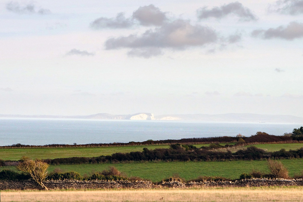 The distant cliffs on the Isle of Wight loom through the haze.