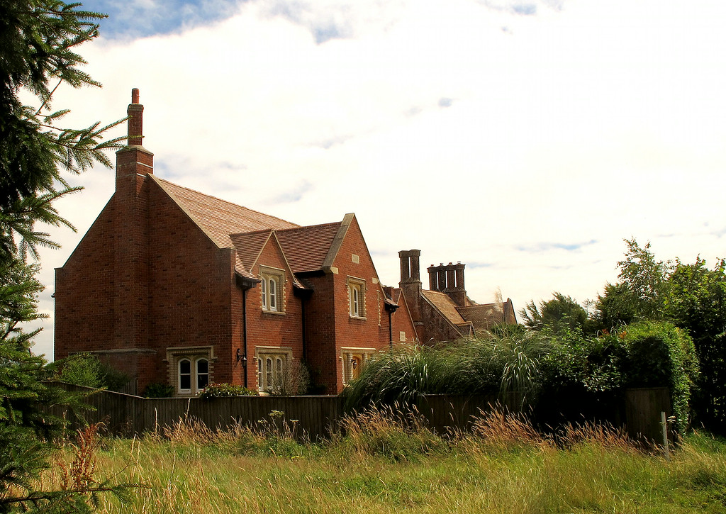 A new house next to an old one at Knighton, well matched except now redundant multiple chimneys.