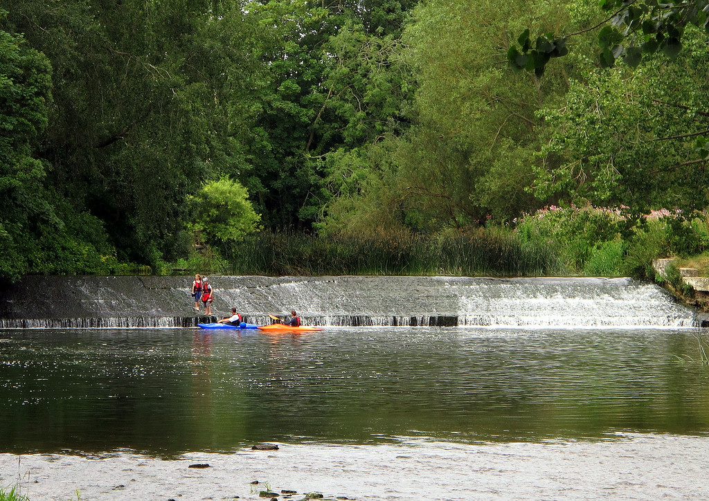 Children having a lovely time on the weir at Canford watched by their parents.