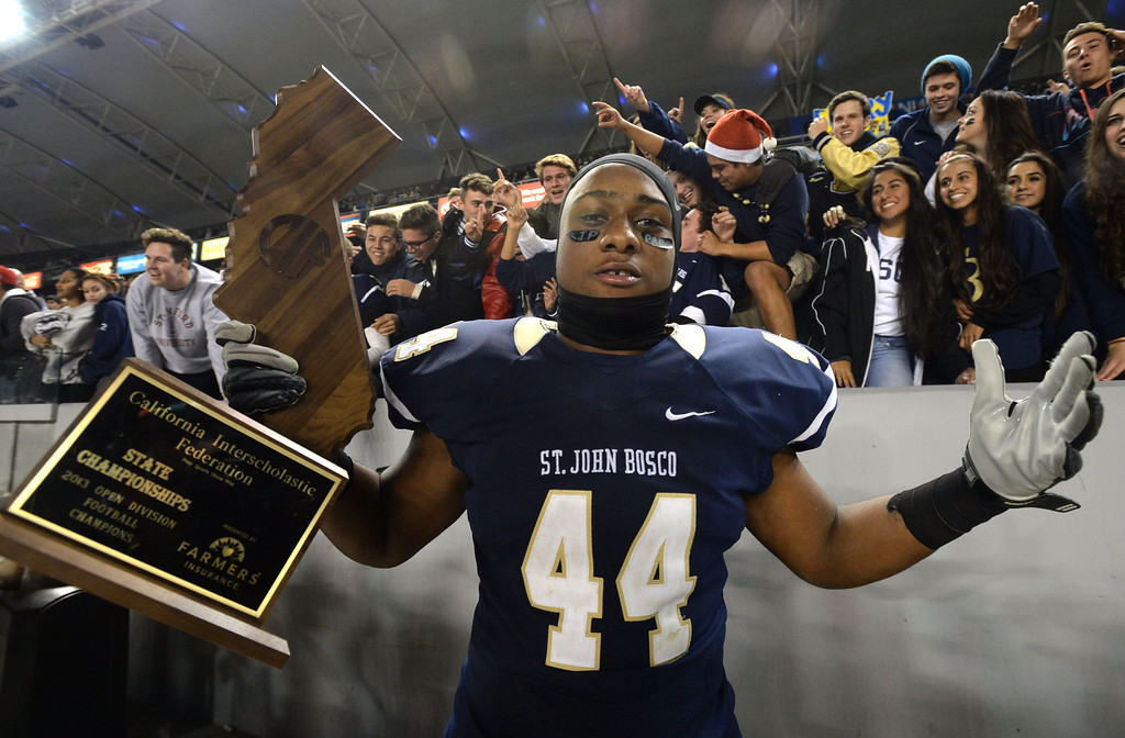 . St. John Bosco\'s Malik Dorton (44) celebrates with the state trophy after beating De La Salle in the CIF State Football Bowl Championships Saturday, December 21, 2013, at the Stub Hub Center in Carson, CA.   Bosco won 20-14. Photo by Steve McCrank/DailyBreeze