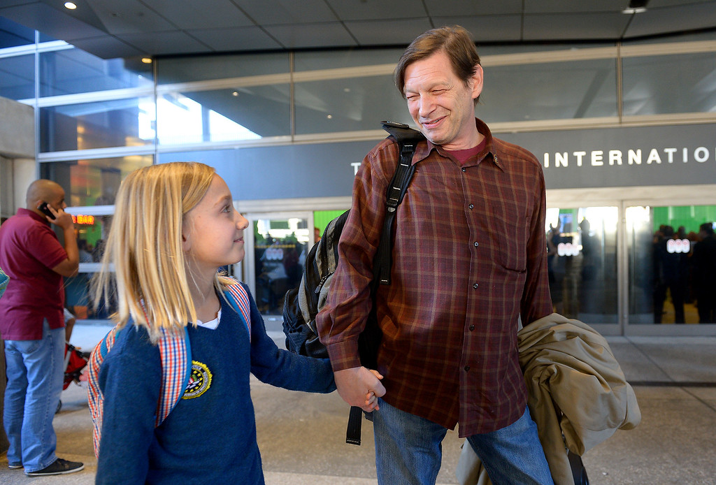 ". Robert Pfeifer and his son Robert ""Jerry\"" Pfeifer, 10, walk at LAX after arriving from France, Saturday, December 28, 2013, after a French court reaffirmed his parental custody. The boys\' mother, Maria Pfeifer, is accused of taking her two sons on a trip to Europe in 2012 and never returning, in violation of custody orders involving the boys\' fathers. (Photo by Michael Owen Baker/L.A. Daily News)"