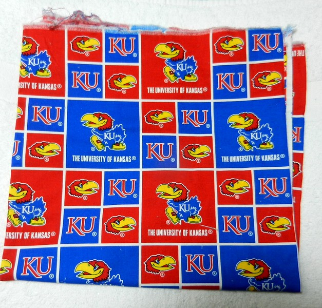 KU squares cotton. Could use the red square with Jayhawk, the Blue square with Jayhawk, the complete square with 4 smaller images, or 2 of the smaller squares offset, or just one of the small squares.