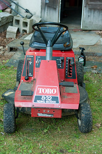 "The Toro riding mower (circa 1986).  We bought this ""as is"" from the seller and with a new blade it runs well.  Walk-out basement door behind."