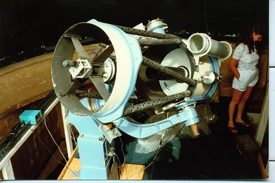 "This view provides a look at the tube assembly. The 18 inch Hyperbolic mirror is covered with a two handled cap. The long black primary baffle tube keeps sky light from ""flooding out"" the image, and is essential to all Cassegrain systems, of which the Ritchey-Cretien design is included .   The 4 vane secondary system is extremely ridged with virtually no flexure. Flexure in a Ritchey-Chretien system is totally unacceptable, as the alignment must be of absolute precision or this will render the optics useless.   The weight of the heavy hyperbolic secondary system has also been carefully counter-balanced by the ""counter weight"" protruding at the end of the spider. Wagman Observatory -Manka Telescope take note of this !!"
