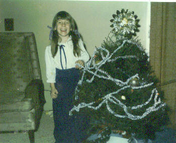 Christy Nebeker with her own surprise first live Christmas tree on Christmas Day 1974, other than the normal fake tree that was put up every year; gift from her two older brothers who snuck out late on Christmas Eve to get it free from a closed tree lot.