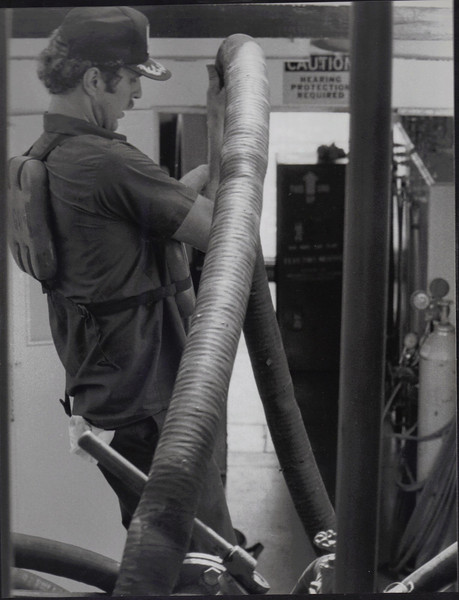 """After loading the boat with about 35 thousand gallons of fuel, Glen JAckson lifts the fuel hose out of the """"Three Rivers Lady."""""""