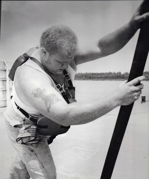 First mate Mark Cunningham makes a routine adjustment to a cable on the barge. Cunningham supervises two deckhands on board.