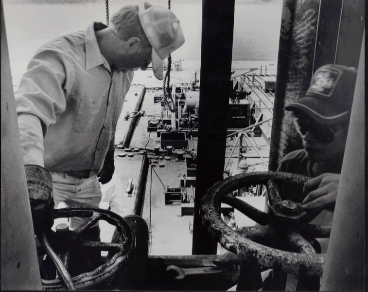 J L Crawford, an independent tanker man and Billy Milligan of Lion Oil make necessary adjustments to the valves before unloading the barge.