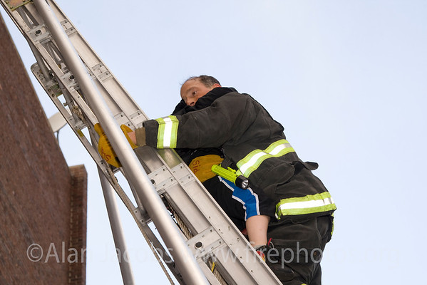 CFD E-55 Fireman Sid Bleustein brings still another child to saftey.