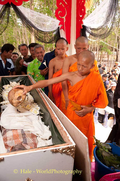 Young Monk Pours Coconut Water On Corpse