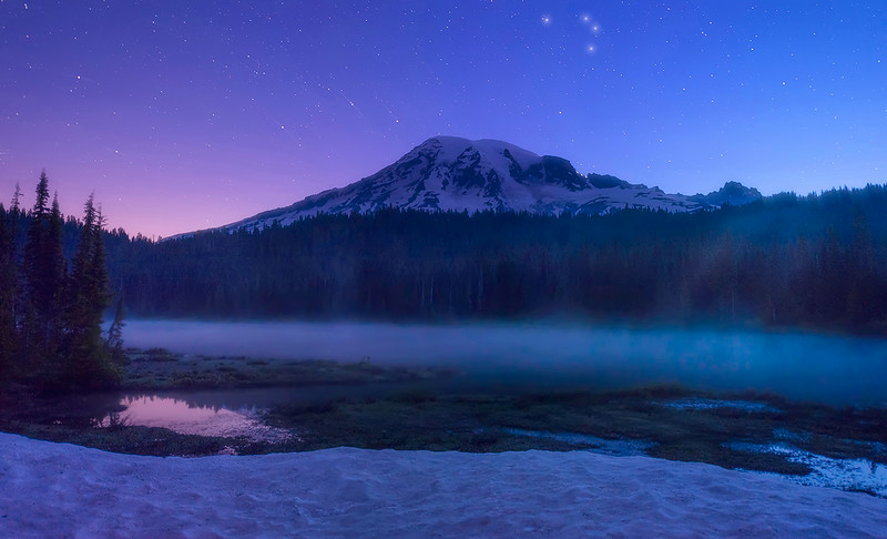 Stars twinkle over a foggy lake at Mount Rainier National Park. Another one of the locations we will visit!
