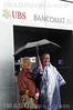 Biel - Bienne: Expo - 02: Rentnerin und Rentner mit Regenschirm vor Bancomat der UBS. Pensionär.<br /> © Patrick Lüthy/IMAGOpress.com