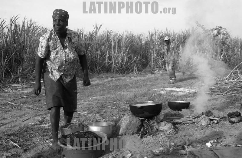 Republica Dominicana - Barahona 15/09/03 : En varias zonas de Republica Dominicana existen plantaciones de cana azucarera . En estos sitios trabajan principalmente Hiatianos  ,en condiciones de explotacion y llevando una vida miserable. En la imagen una mujer haitiana prepara comida para vender a los trabajadores a orillas del canaveral. / Dominican Republic : black woman on a sugar plantation. / Dominikanische Republik : Eine schwarze Arbeiterin bei einer Zuckerplantage. (B/W)<br /> ©  Orlando Barria/LATINPHOTO.org
