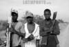 Republica Dominicana - Barahona 15/09/03 : En varias zonas de Republica Dominicana existen plantaciones de cana azucarera . En estos sitios trabajan principalmente Hiatianos  ,en condiciones de explotacion y llevando una vida miserable. En la imagen tres jovenes haitianos muestran sus machetes . / Dominican Republic : black youths on a sugar plantation. / Dominikanische Republik : Schwarze Arbeit bei einer Zuckerplantage. (B/W)<br /> ©  Orlando Barria/LATINPHOTO.org