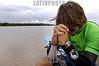 """Brasil : Surfista brasileno Sergio Laus reza antes de pegar una ola de la marea, conocido como pororoca, en el rio Araguari, en el estado norteno de Amapa, Brasil. La pororoca de Araguari es posiblemente el mas peligroso de todos los ondas de marea de la amazonia, temido por los residentes locales para el estrago que causa. Las ondas llegan a la altura de en 2 a 3 metros y alcanza velocidades entre 30 a 50 kilometros por hora. Para cogerlo, las surfista deben saltar de una lancha quando la onda sube el rio. Puesto que la onda ocurre solamente dos veces por el dia, cuando la marea entrante del oceano invierte el flujo del rio, no hay muchas ocasiones de cogerlo. La palabra """"pororoca"""" viene de las palabras de dialecto de las indigenas amazonenses """"poroc poroc"""" que significa  """"destructor"""" o """"gran rafaga"""" Desde el tiempo inmemorial, la gente ha temido el rugido que precede. / Brazil: Brazilian surfer Sergio Laus pauses for a moment before surfing on the tidal bore wave, known as pororoca, on the Araguari River. The Araguari pororoca is possibly the most dangerous of all the Amazonian tidal bores, long feared by locals for wreaking havoc on their communities. wave crests at 2 to 3 meters and races at speeds between 30 to 50 kilometers per hour.  To catch it, surfers must leap from a motorboat as the wave barrels upriver. Since the wave only occurs twice per day when the incoming ocean tide reverses the river flow for a time, there are not many chances to catch it,  The name """"pororoca"""" comes from an Amazonian indigenous dialect meaning """"destroyer"""" or """"great blast.""""  Since time immemorial, people have feared the roar which precedes the wall of water that capsizes boats and washes away anything in its path. Now, however, the people are less fearful and have begun to see the wave as a potential tourist attraction that could generate money in the state of one of the poorest of Brazil. / Brasilien: Surfer in der Region von Pororoca. Abenteuer. © Douglas Engle/LATINPHOTO.org"""
