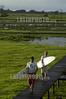 """Brasil : Surfista brasileno Adilton Mariano, en frente, y Marcelo Piu Piu caminan hacia lanchas para pegar una ola de la marea, conocido como pororoca, en el rio Araguari, en el estado norteno de Amapa, Brasil. La pororoca de Araguari es posiblemente el mas peligroso de todos los ondas de marea de la amazonia, temido por los residentes locales para el estrago que causa. Las ondas llegan a la altura de en 2 a 3 metros y alcanza velocidades entre 30 a 50 kilometros por hora. Para cogerlo, las surfista deben saltar de una lancha quando la onda sube el rio. Puesto que la onda ocurre solamente dos veces por el dia, cuando la marea entrante del oceano invierte el flujo del rio, no hay muchas ocasiones de cogerlo. La palabra """"pororoca"""" viene de las palabras de dialecto de las indigenas amazonenses """"poroc porco"""" que significa  """"destructor"""" o """"gran rafaga"""" Desde el tiempo inmemorial, la gente ha temido el rugido que precede. / Brazil: Brazilian surfers Adilton Mariano and Marcelo Piu Piu walk from theid bungalow to motorboats to surf on the tidal bore wave, known as pororoca, on the Araguari River, in Brazil's northern state of Amapa. The Araguari pororoca is possibly the most dangerous of all the Amazonian tidal bores, long feared by locals for wreaking havoc on their communities. wave crests at 2 to 3 meters and races at speeds between 30 to 50 kilometers per hour.  To catch it, surfers must leap from a motorboat as the wave barrels upriver. Since the wave only occurs twice per day when the incoming ocean tide reverses the river flow for a time, there are not many chances to catch it,  The name """"pororoca"""" comes from an Amazonian indigenous dialect meaning """"destroyer"""" or """"great blast.""""  Since time immemorial, people have feared the roar which precedes the wall of water that capsizes boats and washes away anything in its path. / Brasilien: Surfer in der Region des Araguari - Flusses im Norden von Amapa.  Wellenreiter. Sport. Abenteuer. © Douglas Engle/LATINPHOTO.org"""