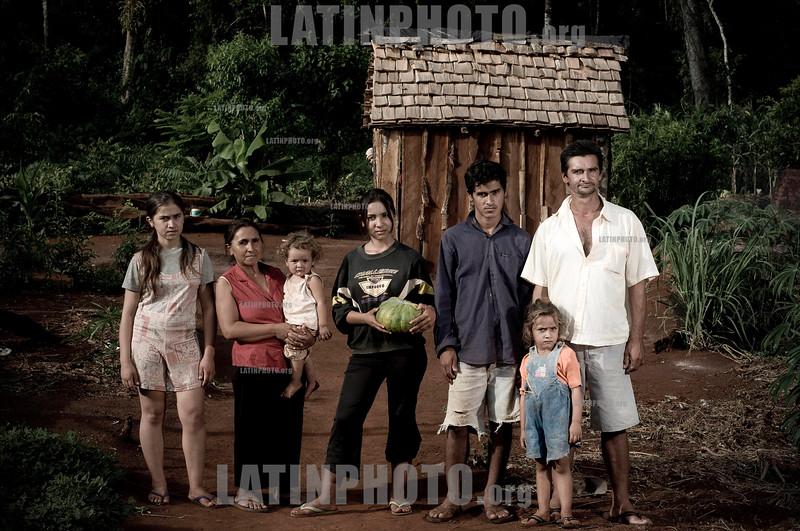 Paraguay: En Paraguay mas de 2 .600.000 hectareas de soja - el doble que en el 2001 - y en el ultimo ano se produjeron 3 ,8 millones de toneladas. Ademas de la expulsion de campesinos, los productos que se utilizan para fumigar son considerados toxicos de alta peligrosidad. El asentamiento 13 de Mayo, en el departamento de Itapua, es el escenario del intento de unas 40 familias por sobrevivir y mantener sus cultivos tradicionales en medio de ese oceano de soja. / It is the history of the settlement 13 de mayo, in the area of Itapua, Paraguay. It is a group of peasant families - about 70 people - who atempt to maintain their identity and their unique relationship with the land, within the framework of the advance of the soy monocultive. There are in Paraguay 2.600.000 hectares of soy - twice as much as in 2001- and in the last year 3.8 millons of tons have been produced, dispite the drought. familia. pobreza. / C'est l'histoire de l'etablissement 13 de Mayo, dans la region de Itapua, Paraguay. C'est un group de familles paysannes - un total de 70 personnes - qui essayent de soutenir leur identite et leur liaison avec la terre, dans le cadre de l'avancee du monocultive du soja. Au Paraguay, il y a 2.600.000 hectares de plantation de soja - deux fois plus que dans l'annee 2001 - et dans l'annee derniere 3.8 millons de tonnes de soja ont ete produits malgre la secheresse. / Sojabauern in Encarnacion. Landwirtschaft. Sojaanbau. Gruppenbild einer Familie vor einer HolzhŸtte. © Sebastian Hacher - Olmo Calvo Rodriguez/LATINPHOTO.org