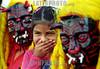 Guatemala: Nina rie mientras observa el baile de los 24 diablos, esta es una actividad parte de las tradiciones en  la region de Antigua . Tradicion, Baile, diablos. / Guatemala: child. mask. larva. / Guatemala: Ein indigenes Mädchen lacht zwischen zwei Larven. Teufelsmasken.