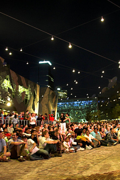 A well ordered crowd, sitting down opposite a big screen and waiting.