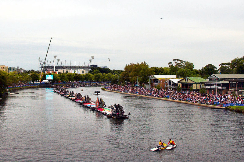 On the evening of the opening of the Games, huge crowds gathered by the Yarra, well before the start.<br /> <br /> At this stage Princes Bridge (from where this photo was quickly taken) was a 'no stop' pedestrian zone. Dozens of guards and volunteers stood on the bridge to ensure people kept moving. <br /> <br /> In this picture you can see two jet skis (foreground) which had cameras for televising the ceremony. Large screens can be seen by the river so people could see the ceremony in the MCG (rear of picture) and a number of helicopters were circling.
