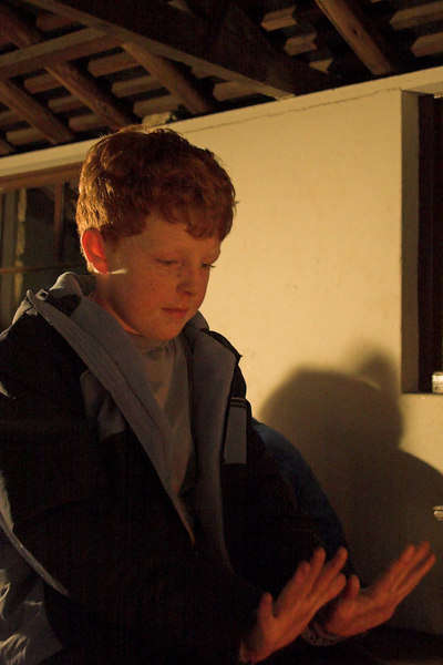 Lachlan warms his hands by the fire.