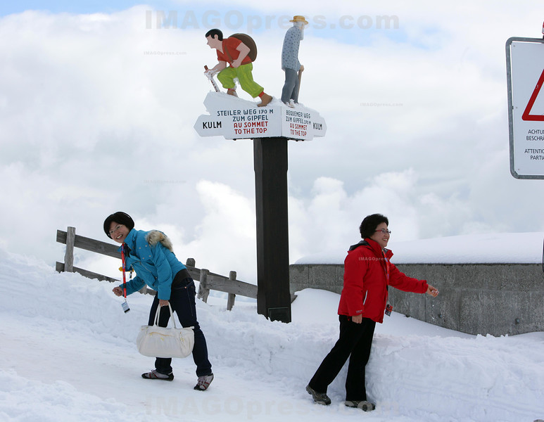 Touristinnen aus Südkorea kopieren zwei Wanderfiguren aus Holz auf Rigi - Kulm.
