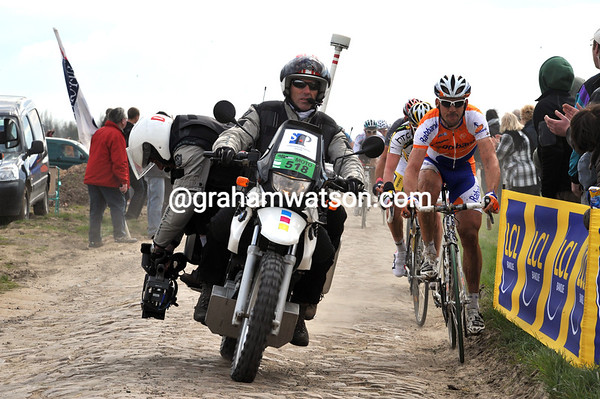 A TV motorbike is squeezing the escapers as the peloton moves in...