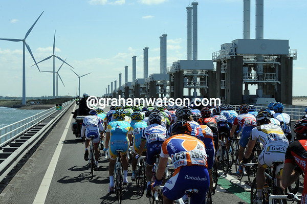 The leading group crosses the final bridge of the day, but they are about to be caught as the wind changes...