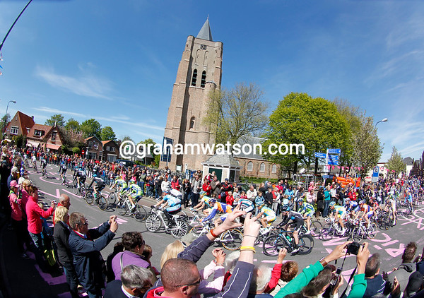 The peloton is about to regroup as it crosses a Zeeland village...
